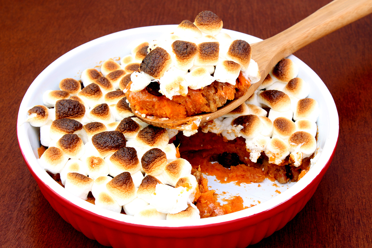 A photograph of a sweet potato casserole with pecans and topped with toasted mini marshmallows.